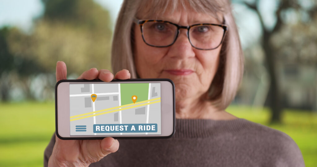 Mature white female holding up smartphone to camera with rideshare app open
